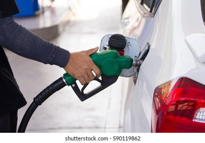 male employees controlled the fuel pump  with Fuel nozzles adding gasoline fuel in car at a pump gas station