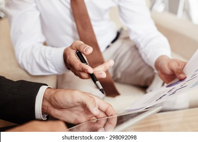 Male employees discussing paper and electronic documents