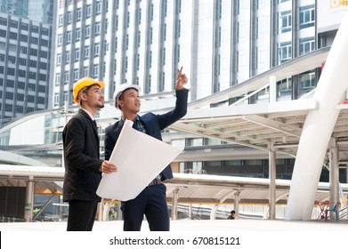 Male employees wear yellow helmet, holding a pose drawings. Hand pointing to construction. The progress of construction. Shows confidence and conviction. negotiation Successful and complete deal conce