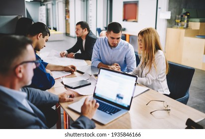 Male employer connecting to office internet for checking banking account during office brainstorming with colleagues, businessman using netbook application for browsing financial report on website
