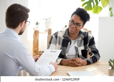 Male employer holding resume talking with African American female job candidate at interview, black millennial girl recruitment process, speak with HR manager, businessman consider applicant cv