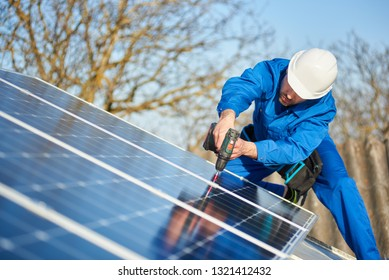 Male engineer in blue suit and protective helmet installing stand-alone solar photovoltaic panel system using screwdriver. Professional electrician mounting blue solar module on roof of modern house