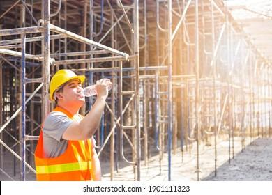 Männlicher Ingenieur Trinkwasser an einem Sommertag auf dem Gebäude im Bau
