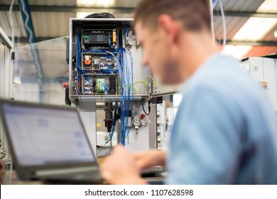 Male Engineer In Factory Using Laptop Computer