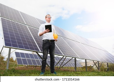 Male engineer in helmet with tablet in hands standing near solar panels. Concept ecology protection.
