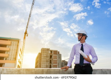 male engineer holds a blue print. Building inspection