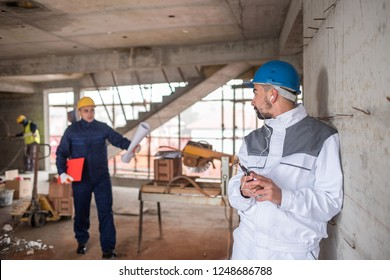 Male engineer ignoring his co-workers and his duty to listen music on headphones