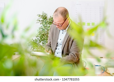 Male engineer making plans on notepad while sitting on desk at workplace