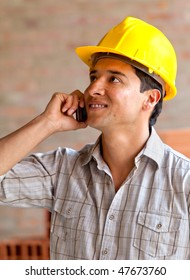 male engineer smiling on the phone in a construction site