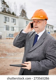 Male engineer uses cell phone, he wearing the suit and the hard hat, house construction site on background