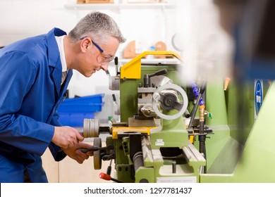 Male engineer using lathe in workshop