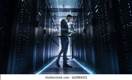 Male IT Engineer Walking and Working in Data Center Corridor. She is Holding Tablet Computer. She is Blurred in Motion.