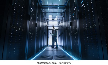 Male IT Engineer Walking and Working in Data Center Corridor. She is Holding Tablet Computer. He is Blurred in Motion.