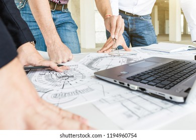 male engineers, architects working at the desk in helmets. Drawings, laptop, roulette on the desktop. Reception and supervision of building construction