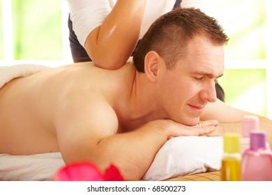 Male enjoying kind of Thai massage treatment with female hand back