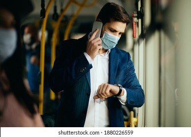 Male entrepreneur communicating over mobile phone and looking at time on his wristwatch while wearing face mask and commuting to work by bus.