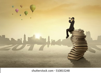 Male entrepreneur sitting on a pile of books while looking to the future by using binoculars