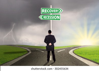 Male entrepreneur standing on the road and look at a signpost while choosing the road to recovery or recession finance