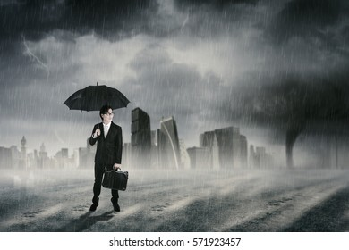Male entrepreneur standing on the road while holding umbrella under the rainy day