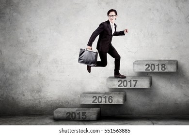 Male entrepreneur stepping on the stairs with number 2017 toward 2018 while carrying a briefcase