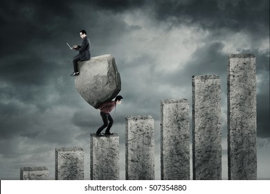 Male entrepreneur walking on chart while carrying a big rock and his partner sitting on the rock with laptop