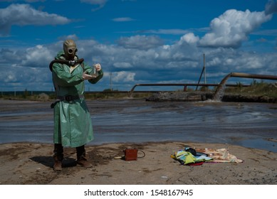 A male environmentalist in a green protective suit and gas mask takes a sample of water in a polluted lake for research. Waste production. Scientist doing toxicological study of toxic waste.