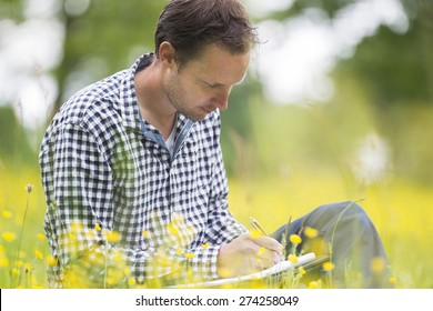 Male environmentalist writing on notepad while sitting in park