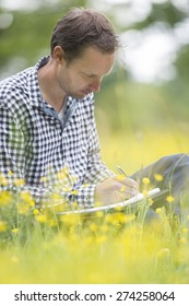 Male environmentalist writing on notepad while sitting on field