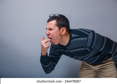male of European appearance brunette put his fingers in his mouth on a gray background, vomiting