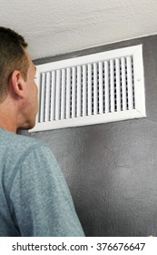 Male examines an indoor air duct register for dirt to understand if he should get it cleaned. One guy in his forties peers into and inspects a furnace central heating vent.