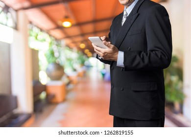 Male executive or Businessman use Smartphone while standing walkway or Corridor Modern Building or Hotel as Technology working on the go Concept