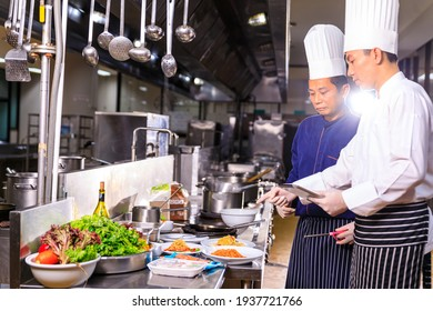 The male executive chef discussing the menu with his colleague in the kitchen.Food and restaurant concept.