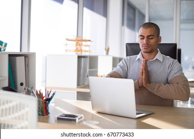 Male executive doing yoga in office