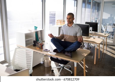 Male executive doing yoga on desk in office