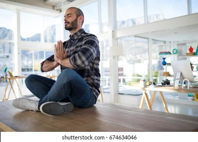 Male executive performing yoga on a table in the office
