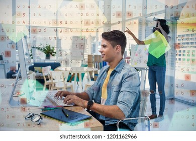 Male executive using computer with colleague in virtual reality headset at creative office