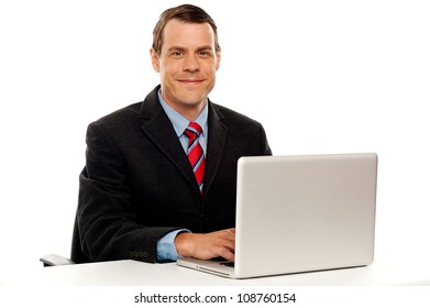 Male executive at work desk operating laptop and smiling camera