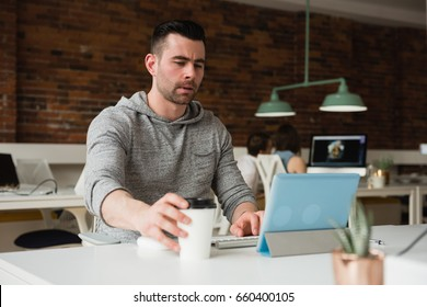 Male executive working on digital tablet while having coffee in office