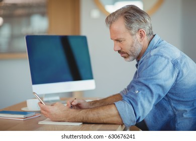 Male executive writing in organizer while using mobile phone in office