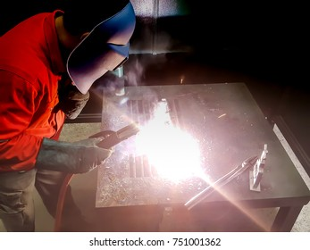 Male in face mask welds with argon-arc welding (selective focus)