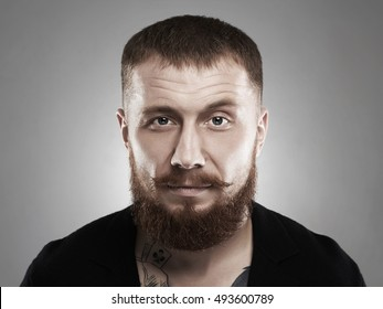 male face with mustache and beard.bearded brutal criminal with tattoo
