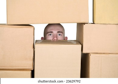 Male face in pile of cardboard boxes on a white