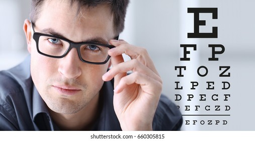 male face with spectacles on eyesight test chart background, eye examination ophthalmology concept