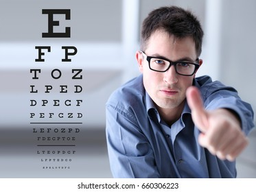 male face with spectacles on eyesight test chart background, showing like hand, eye examination ophthalmology concept