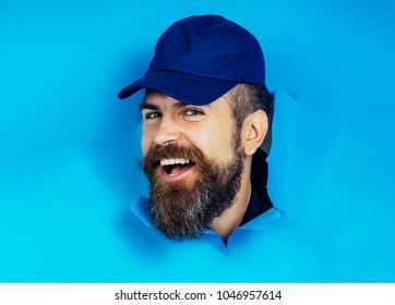 Male face through hole in blue paper. Bearded man in cap watches through hole in paper. Attractive man with beard and mustache breaking paper. Copy space for advertising. Discount, sale, season sales.