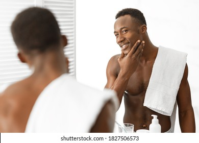 Male Facial Skincare. Attractive Muscular Black Guy Touching Smooth Well-Shaved Face Looking In Mirror Standing Shirtless In Modern Bathroom Indoor. Male Beauty Routine, Care For Skin After Shaving