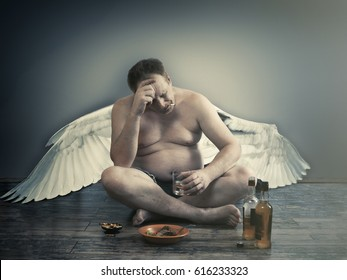 Male fallen angel with alcohol and a cigarette sitting on the floor. Habits, way of life, the temptations and trials