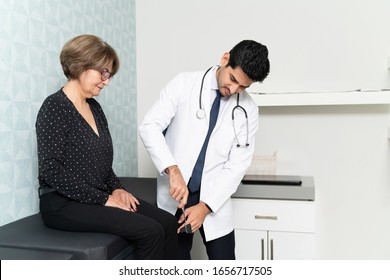Male family doctor using reflex hammer to check reflexes of senior woman