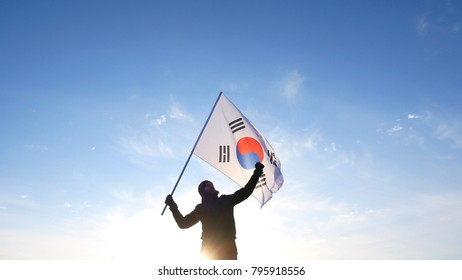 Male fan with South Korean flag rejoices and supports athletes.