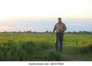 Male farmer checks his fields with crops